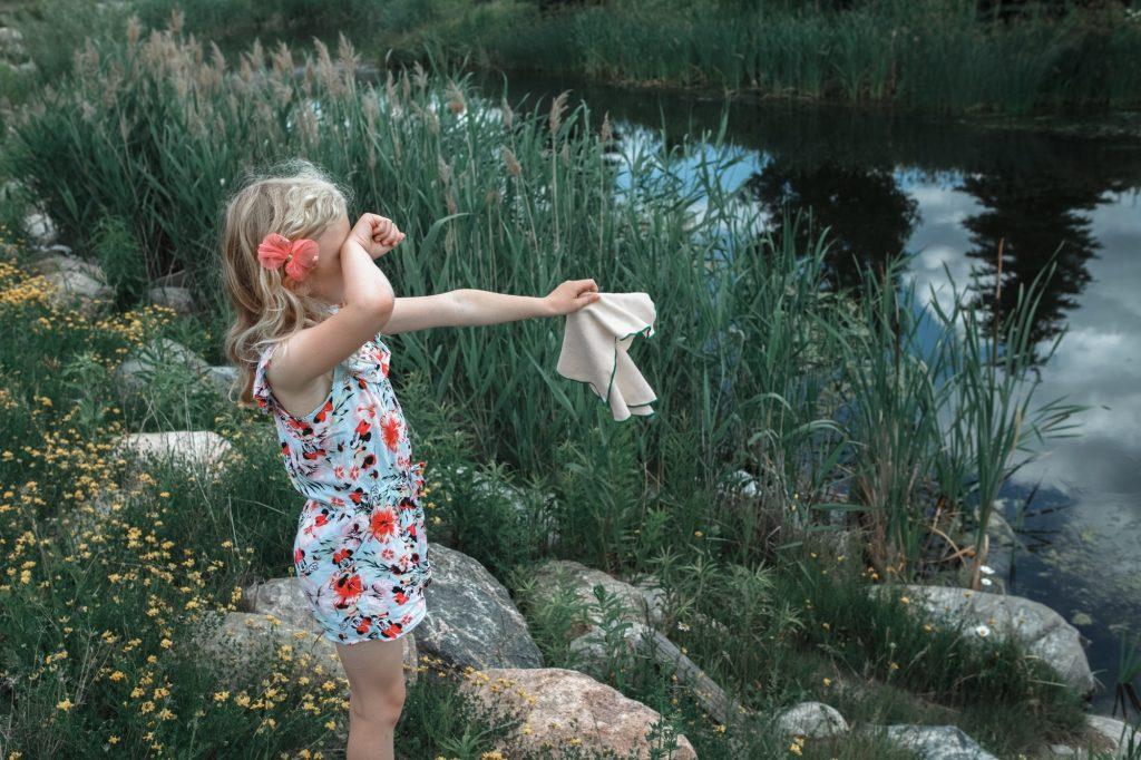Funny sad upset girl waving white neckcloth napkin for farewell goodbye to countryside lake pond
